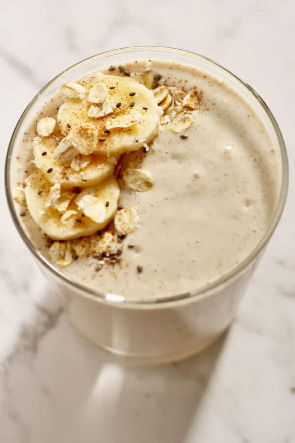 banana oat smoothie in a glass topped with banana slices, cinnamon, rolled oats and chia seeds