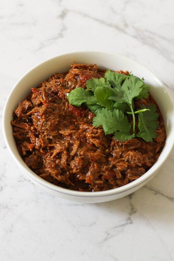 shredded mexican beef in a white bowl.