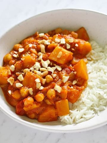 a white bowl filled with pumpkin chickpea curry and rice