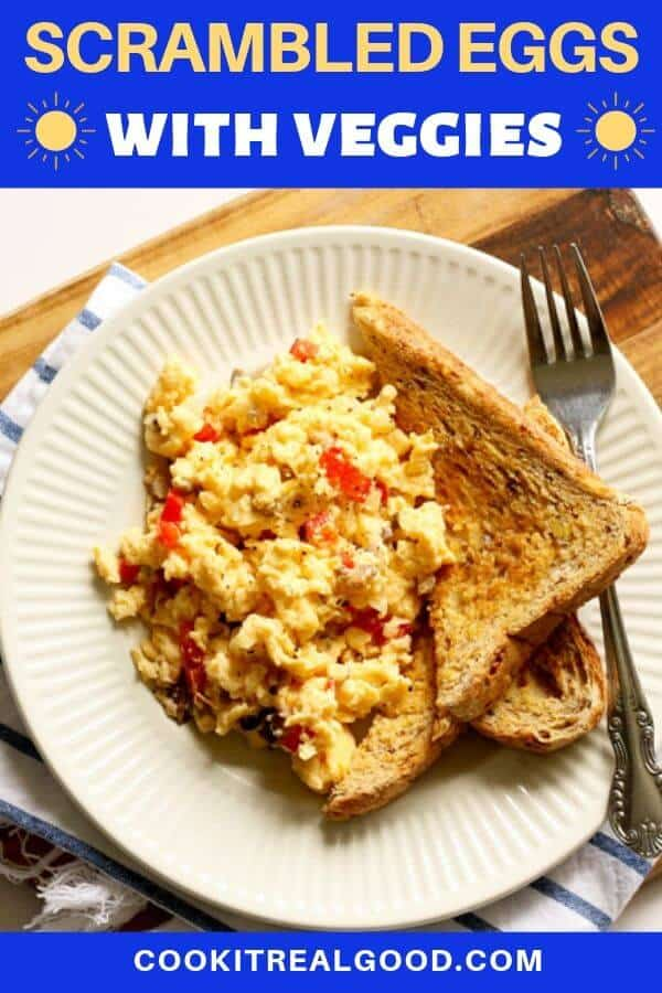 scrambled eggs on a white plate with toast.