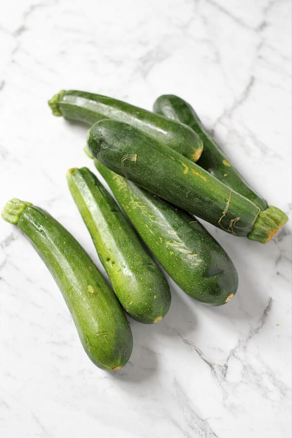 6 zucchinis laying on a white marble background.