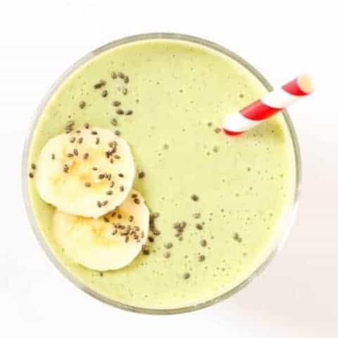 green smoothie in a glass topped with chia seeds and banana slices