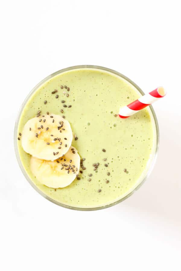 spinach mango smoothie in glass with red straw and banana slices on top
