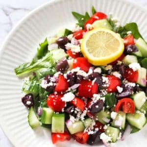 close up image of greek salad topped with lemon slice