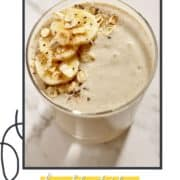 """smoothie in a glass with banana slices and oats on top and text overlay """"banana oatmeal smoothie""""."""