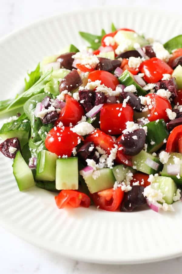 close up image of a greek salad on a white plate