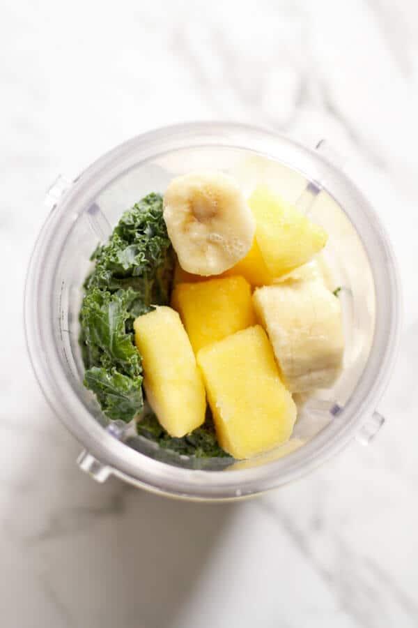 Kale Pineapple Smoothie ingredients in a blender cup