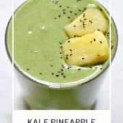 "green smoothie in a glass with text overlay ""kale pineapple smoothie""."