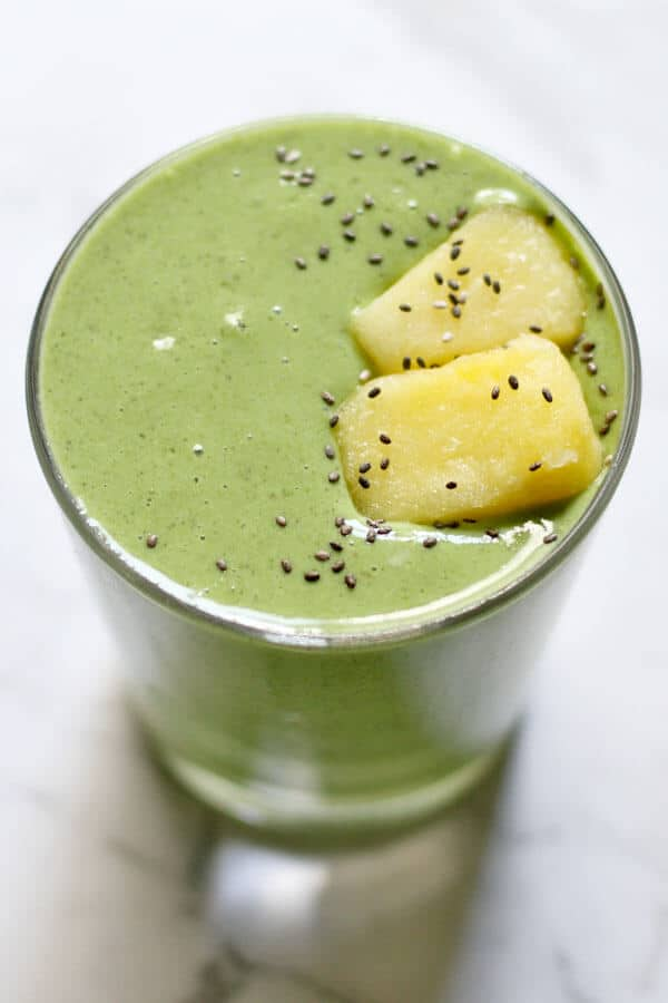 Kale Pineapple Smoothie topped with pineapple pieces and chia seeds