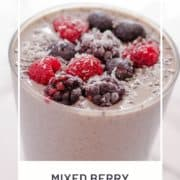 """purple smoothie topped with berries with text overlay """"mixed berry smoothie""""."""