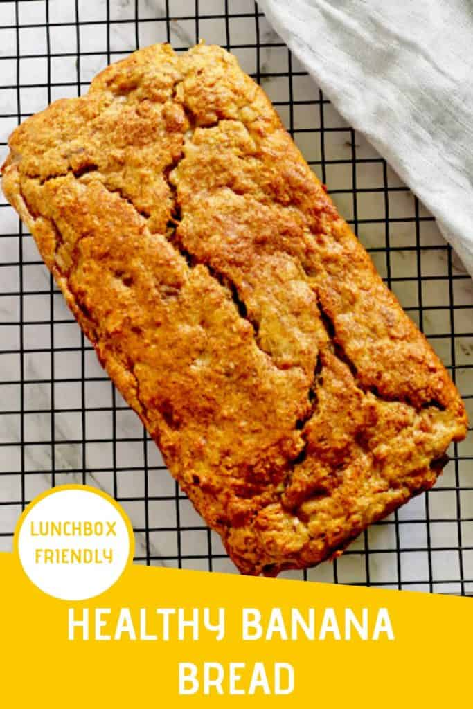 """unsliced banana bread loaf sitting on top of a cooling rack with text overlay that reads """"healthy banana bread - lunchbox approved"""""""
