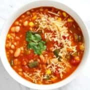 vegetable barley soup topped with parmesan cheese and coriander