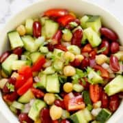 "salad in a bowl with text overlay ""chickpea & kidney bean salad""."