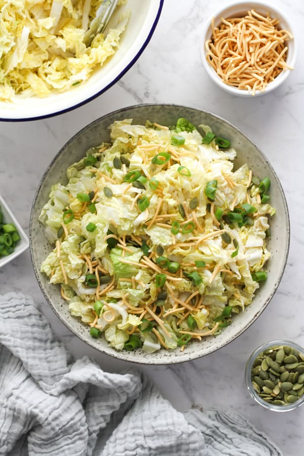 salad in a large bowl surrounded by small bowls of pepitas, noodles and green onions.
