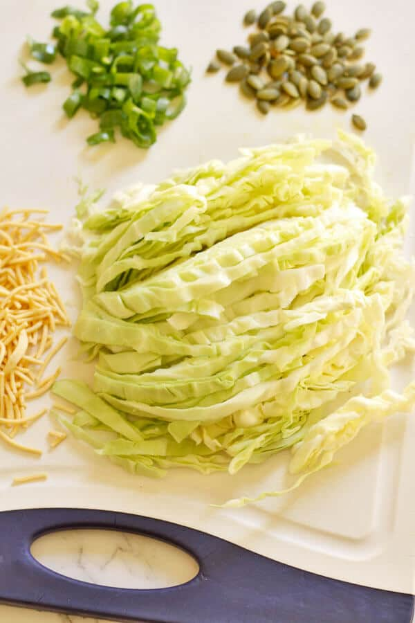 cabbage and crunchy noodle salad ingredients on a chopping board