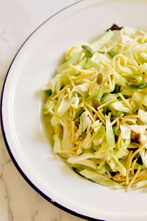 cabbage and crunchy noodle salad closeup on a white plate