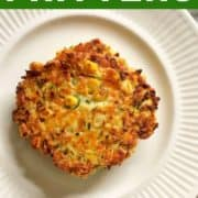 """fritters stacked on a white plate with text overlay """"zucchini & halloumi fritters""""."""