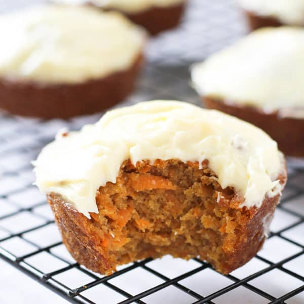 carrot cake cupcakes sitting on a cooling rack, with one cupcake front and centre with a bite missing