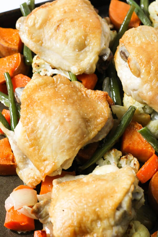 crispy baked chicken thighs on top of a bed of vegetables.
