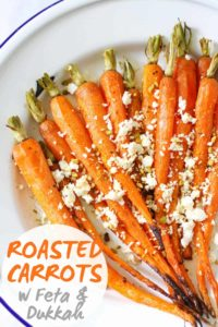 "roasted carrots with feta and dukkah on a white plate with text overlay that reads ""roasted carrots with feta and dukkah"""