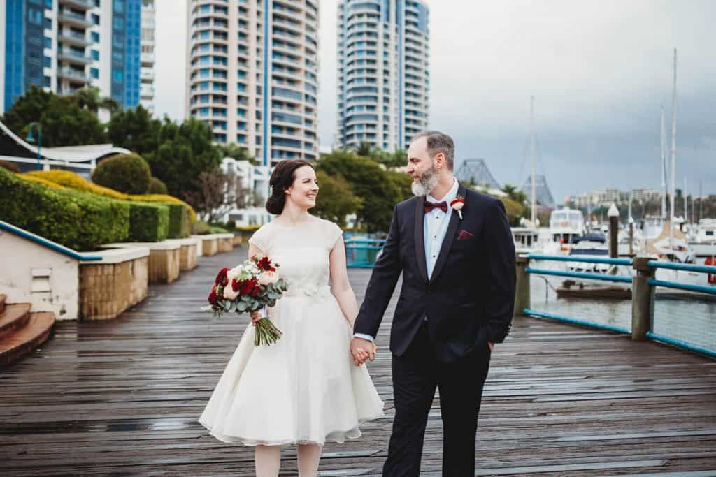photo of a man in a black suit and a women in a short white wedding dress walking hand in hand down a boardwalk