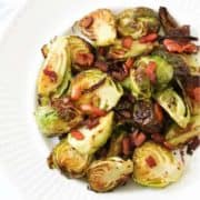 a plate of roasted brussels sprouts with bacon on a white plate