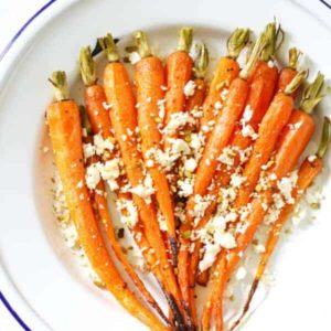 roasted carrots with feta and dukkah on a white plate