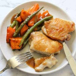 crispy chicken thighs and vegetables on a white plate