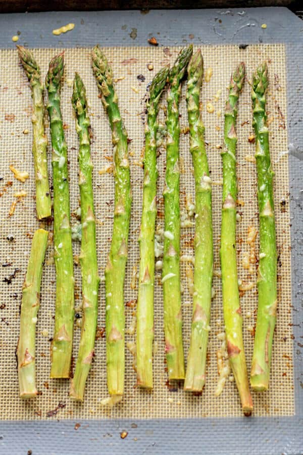 cooked asparagus spears laid out in a single layer on a baking tray covered in parmesan cheese and minced garlic