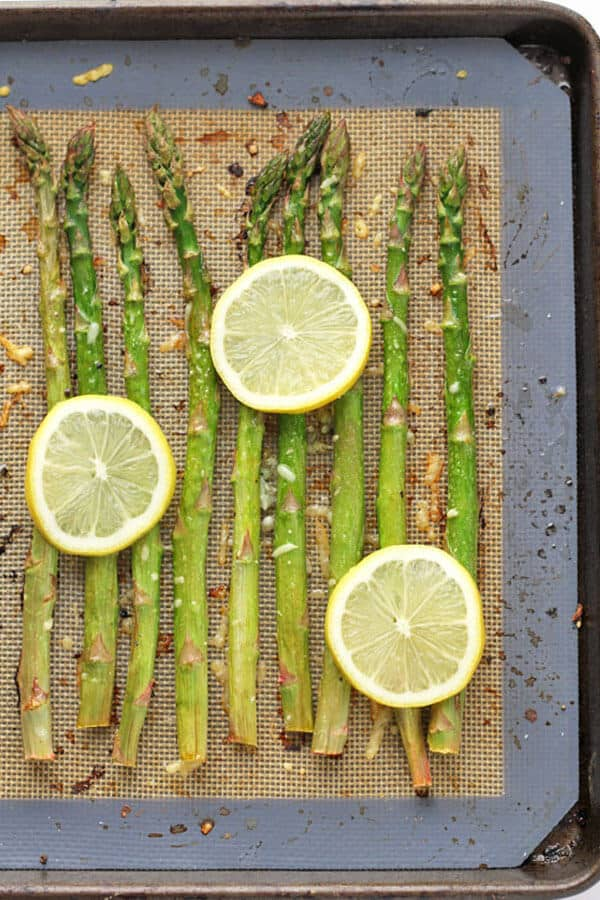 asparagus spears laid out in a single layer on a baking tray covered in parmesan cheese, minced garlic and lemon slices