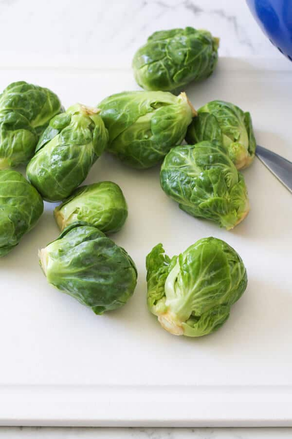 brussels sprouts scattered on a cutting board