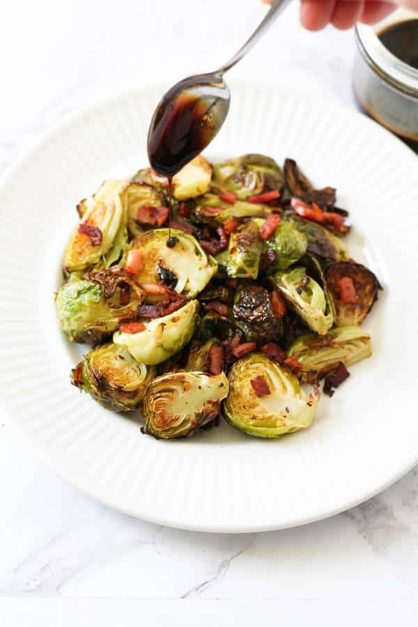 a spoon held above a plate of roasted brussels sprouts drizzling balsamic glaze over the vegetables