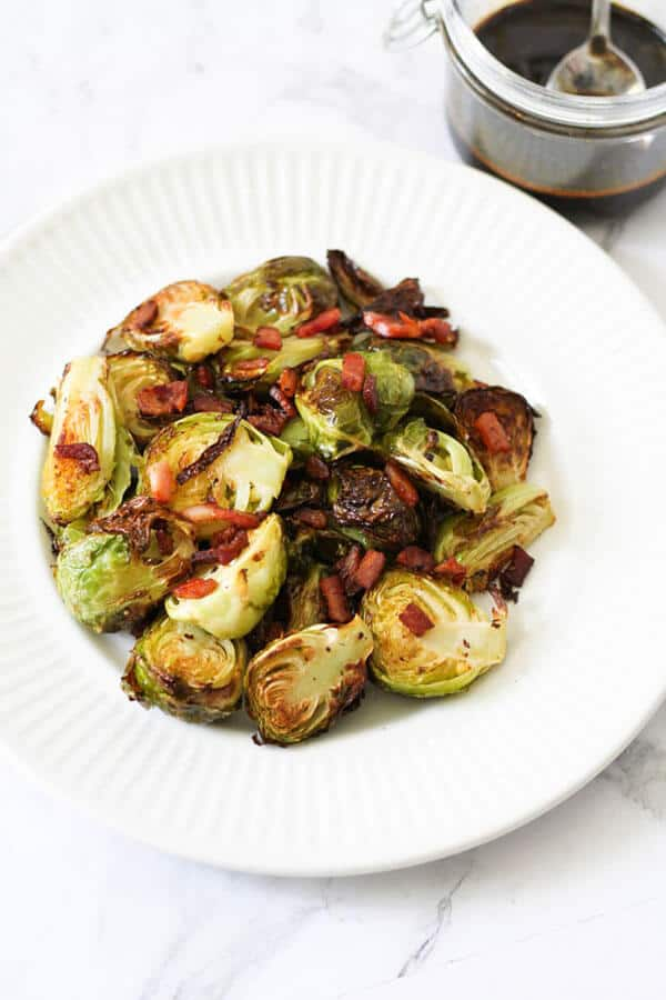 roasted brussels sprouts with bacon on a white plate with a jar of balsamic glaze in the background