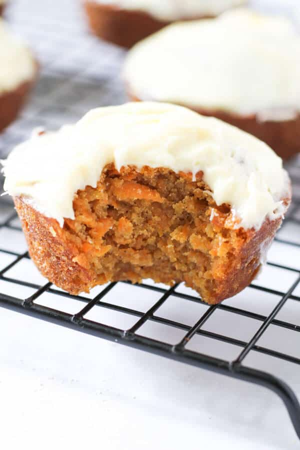 carrot cupcake with white frosting sitting on a cooling rack with a bit taken out of it
