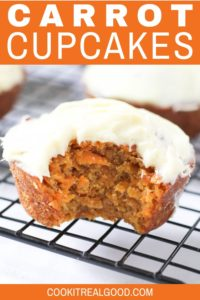 carrot cupcake with a bite removed on a wire cooling rack.