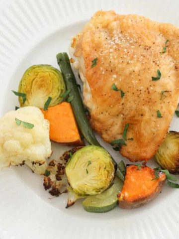 crispy baked chicken thigh and vegetables on a white plate.