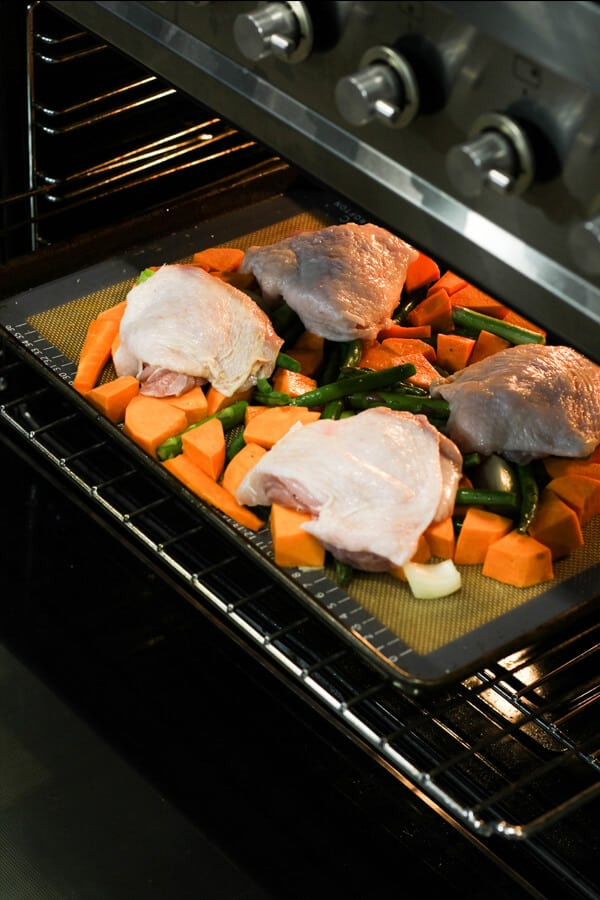 tray of chicken thighs and vegetables being placed in an oven