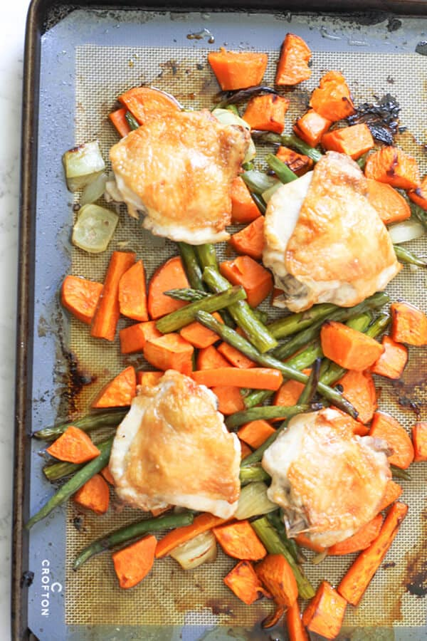cooked crispy chicken thighs and vegetables on a sheet pan