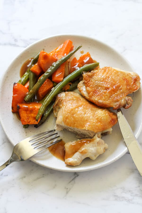 crispy chicken thigh and vegetables with gravy on a white plate