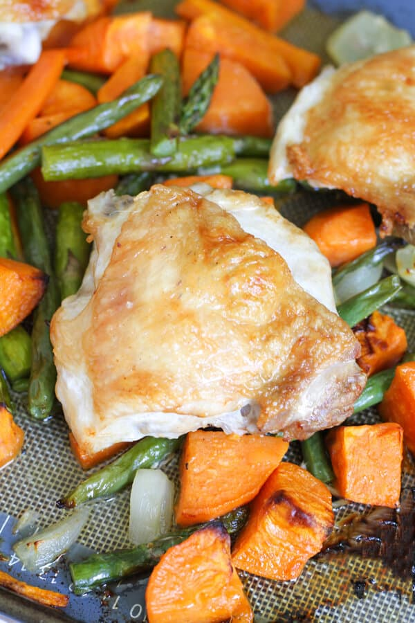 close up of crispy chicken thigh and vegetables on a baking tray
