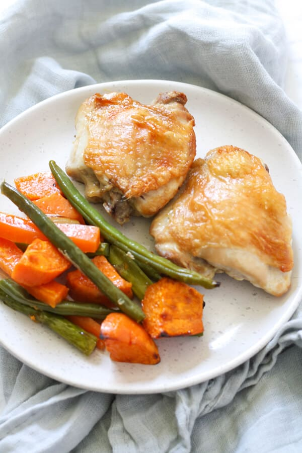 crispy baked chicken thighs and vegetables on a white plate