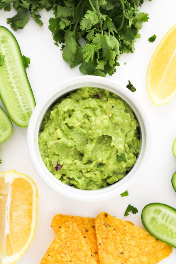healthy guacamole in a white bowl surrounded by ingredients.