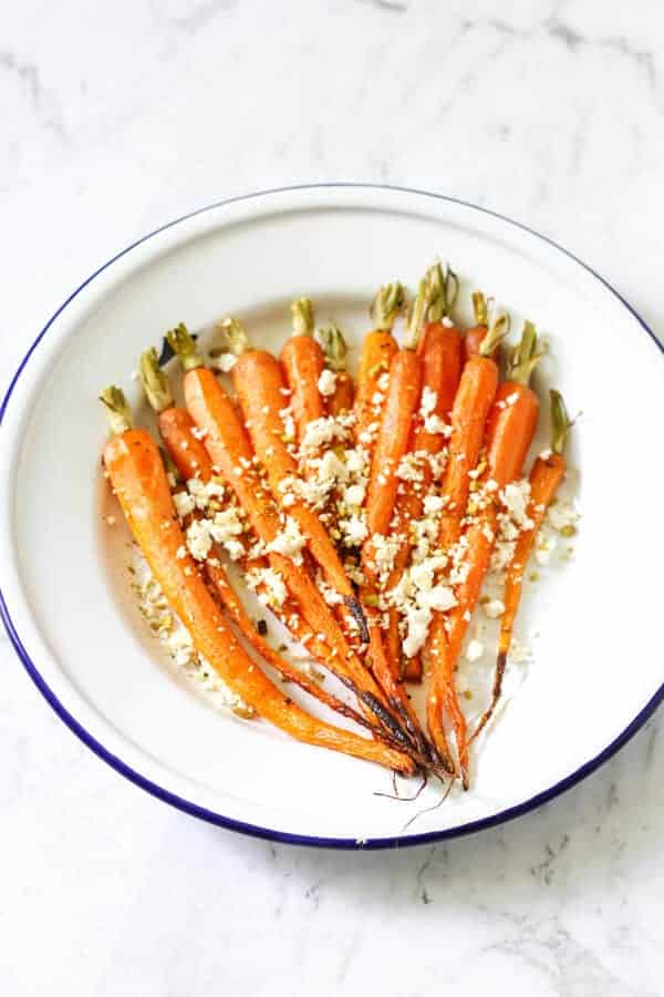 roasted carrots on a white plate with feta and dukkah sprinkled on top
