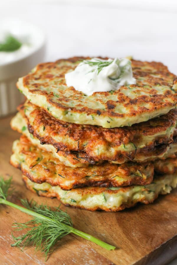 a stack of zucchini fritters with tzatziki pooled on top
