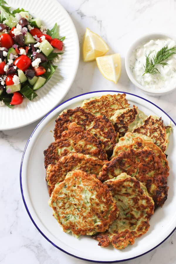a plate of zucchini fritters flanked by a bowl of tzatziki and a plate of greek salad