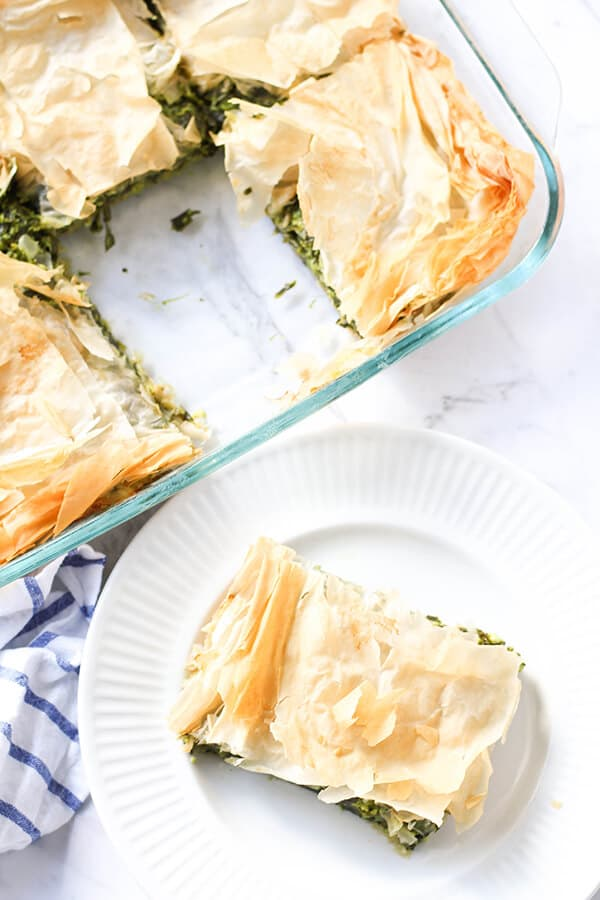 a slice of spanakopita on a white plate with a tray on spanakopita behind.