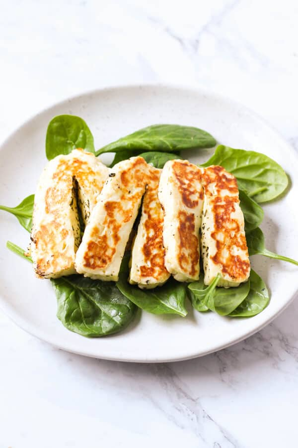 grilled halloumi on a bed of spinach leaves.