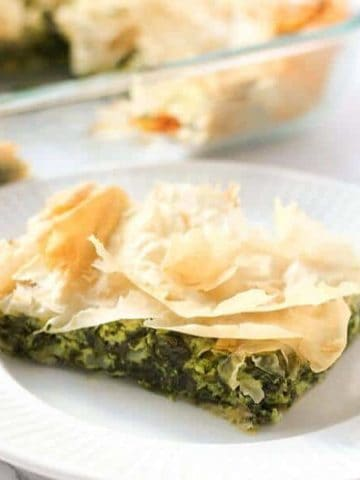 a slice of spanakopita on a white plate
