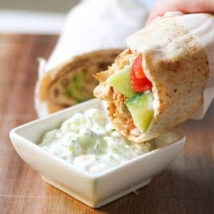 hand dipping a chicken gyro into a bowl of tzatziki sauce