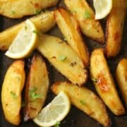 greek potatoes on a baking tray with lemon slices and parsley on top.